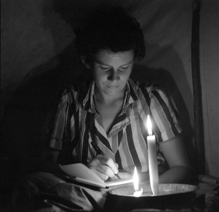 Anna Brown writing in her diary by candlelight at a camp near Fraser River, British Columbia Credit: Rosemary Gilliat Source: Library and Archives Canada