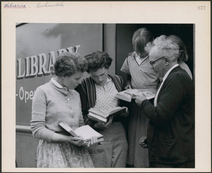 Teachers and students of a one-room school house in northwestern Ontario reading books outside a Bookmobile. On