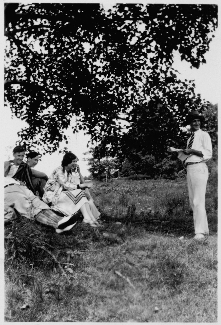 Wilson P. MacDonald reading to a group of people under a tree.