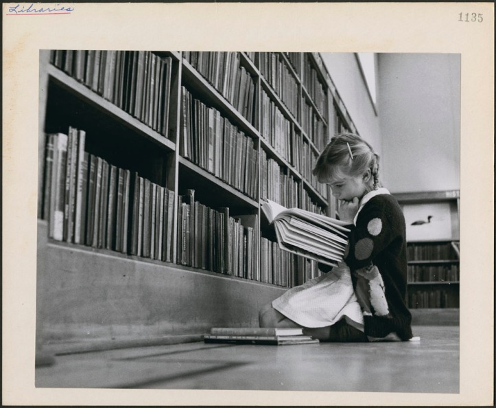 Young girl reading a book. Central Circulating Library at College and St. George streets, Toronto. Photo National Film Board of Canada.