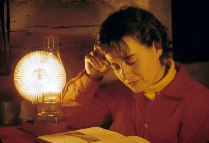 Young woman reading by the light of a kerosene lamp. Shilly Shally Lodge, Gatineau Park. gilliat